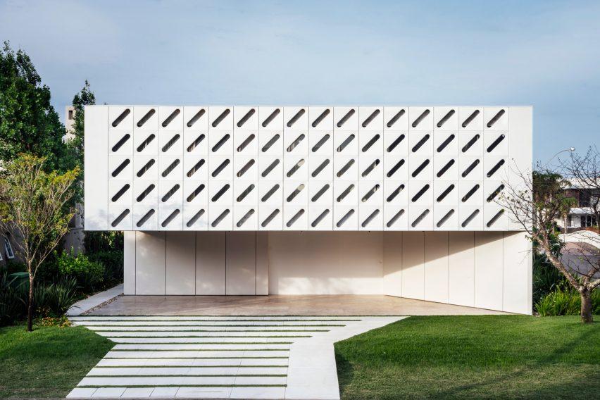 Диагональные прорези прокалывают белые ставни, обертывающие Casa Ventura от Arquitetura Nacional