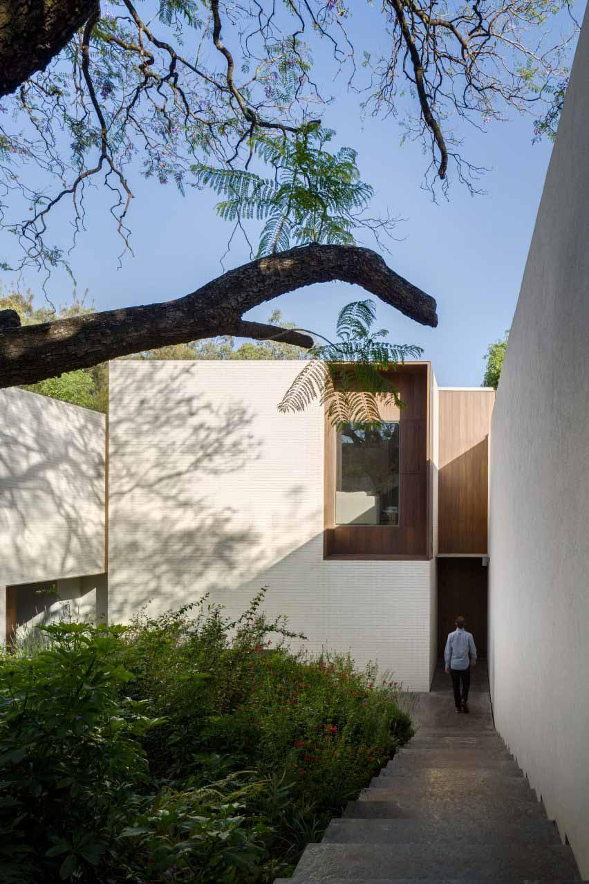 Белая кирпичная кладка охватывает сады дома от Manuel Cervantes Estudio
