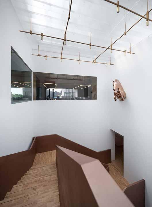 окно в крыше наверху приносит много солнечного света в атриум. Изображение © Qingshan Wu