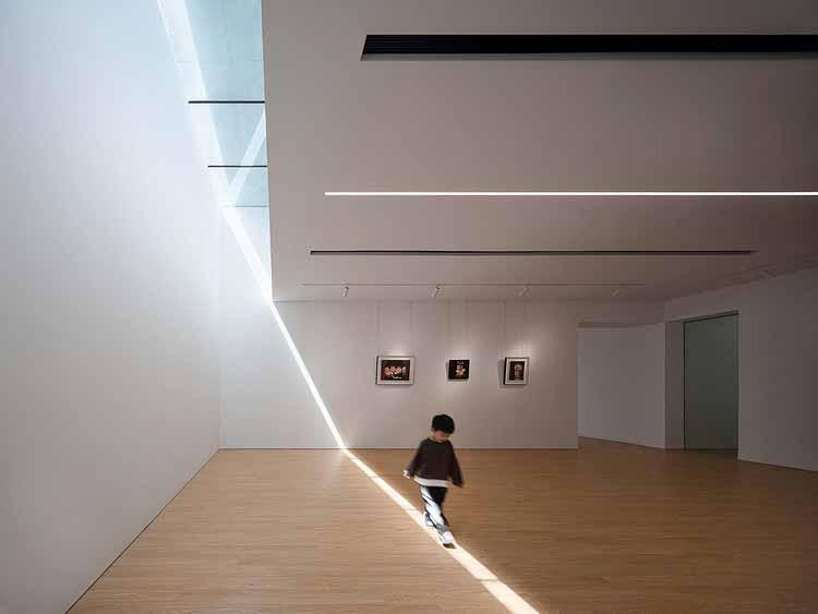 выставочное пространство с рассеянным светом, проникающим через световой люк. Изображение © Qingshan Wu