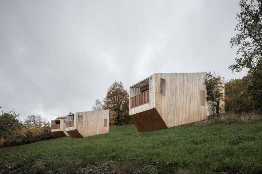 Деревянные домики разбросаны по траве