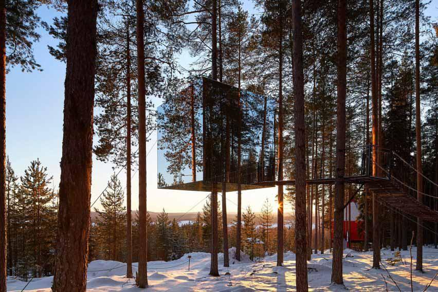 Зеркальная кабина, расположенная над землей, гармонирует с небом и деревьями
