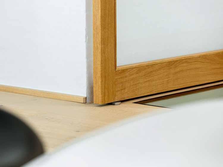 Напольная плита FritsJurgens из нержавеющей стали под поворотной дверью. Шарнирная петля спрятана в деревянной дверной коробке, на верхней части плиты пола. Изображение © FritsJurgens