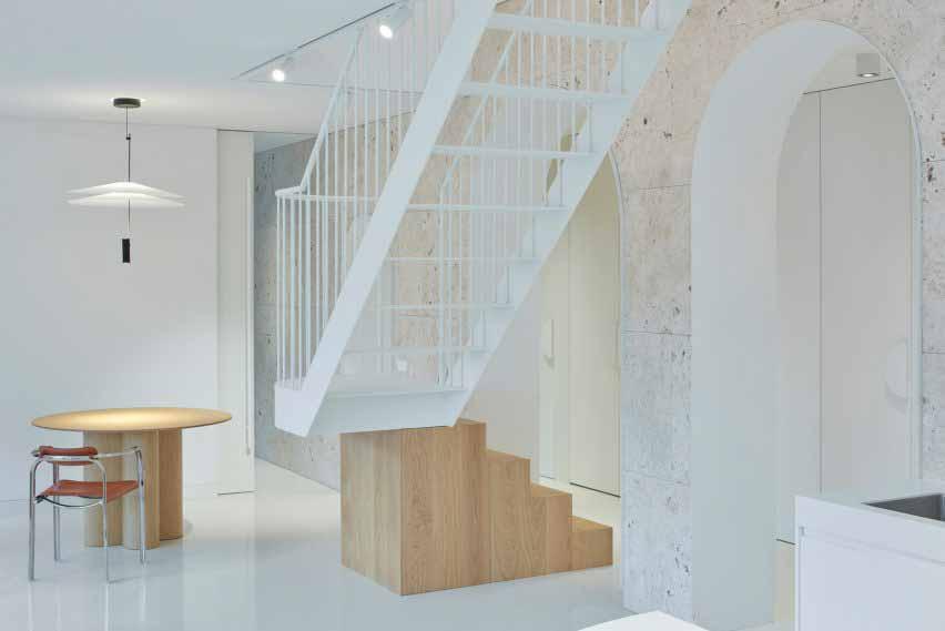 Первый этаж квартиры в Вильнюсе от 2XJ со стеной из травертина и лестницей из дерева и стали.