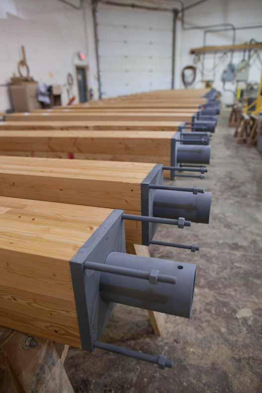 Клееные балки предварительно просверлены, а соединения установлены на заводе. Изображение © Brudder Productions. Предоставлено naturallywood.com