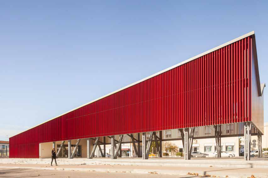 Павильон, облицованный красными алюминиевыми планками.