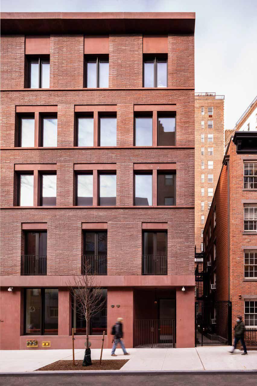 Красный кирпич и цветной бетонный фасад жилого дома