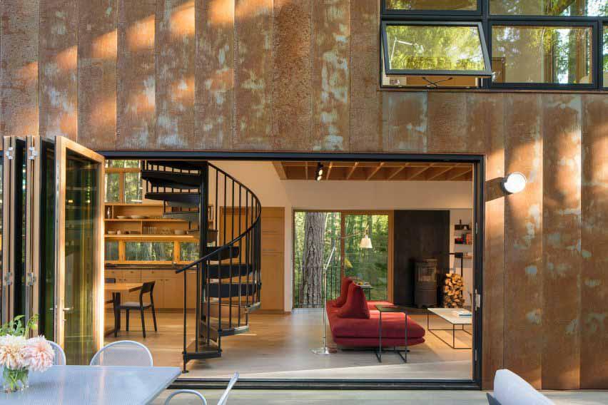 Дом из кортеновской стали расположен в лесу.