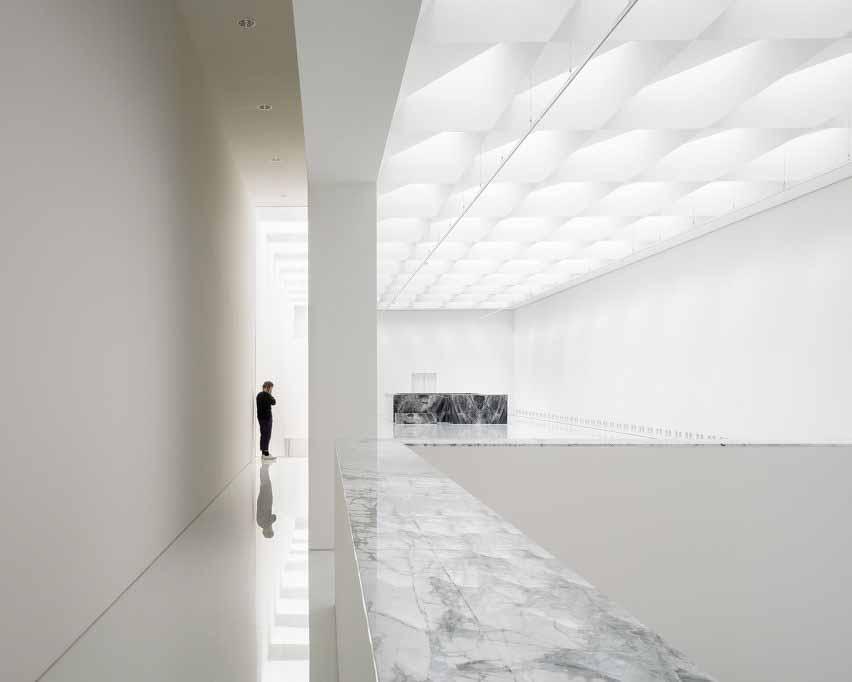 Выставочный зал в современном расширении музея от Kaan Architecten с белыми глянцевыми полами и мраморной отделкой