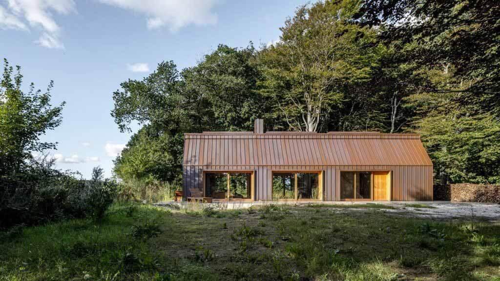 Дом автора — обшитая медью хижина в датском лесу.