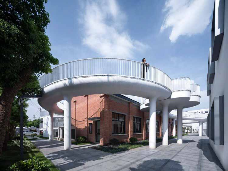 Фабрика вышитой одежды района Цзяннань / Minax Architects, коридор из облаков окружает старое здание.  Изображение © Qingshan Wu