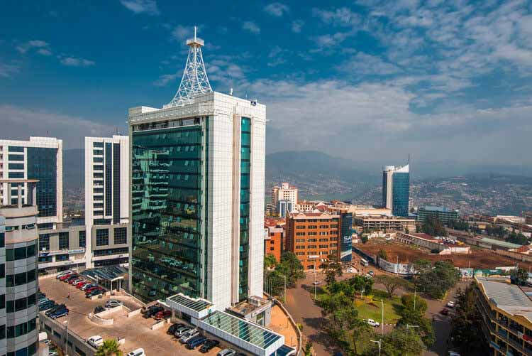 Как «умные» города могут усугубить несправедливость, Кигали, Руанда - 21 сентября 2018 г .: широкий вид на центр города с Pension Plaza на переднем плане и городской башней Кигали на заднем плане на фоне далеких синих холмов.  Изображение через Shutterstock / Дженнифер Софи